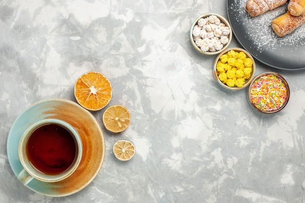 Top view of cup of tea with candies and bagels on white surface