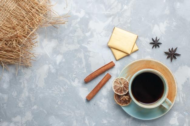 Vista dall'alto tazza di tè con caramelle e cannella sulla colazione colore caramella tè scrivania leggera