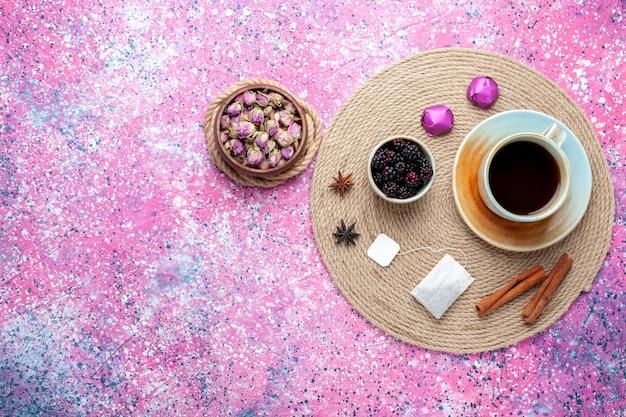 Vista dall'alto tazza di tè con caramelle e cannella su sfondo rosa.