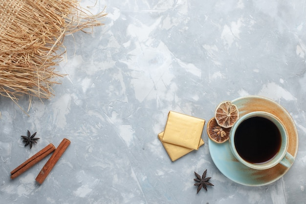 Vista dall'alto tazza di tè con caramelle e cannella sulla colazione colore caramella tè scrivania bianca
