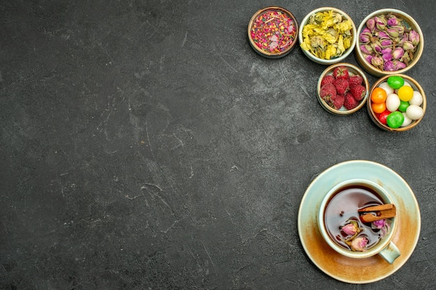 Top view cup of tea with candies and flowers on a dark space