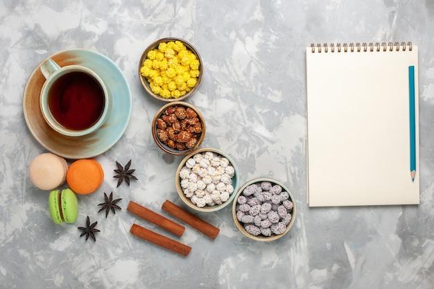 Vista dall'alto tazza di tè con caramelle e macarons francesi sulla scrivania bianco chiaro