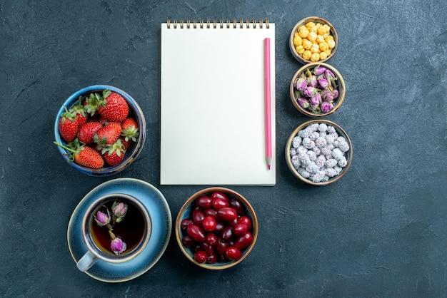 Vista dall'alto tazza di tè con caramelle e frutta su spazio grigio
