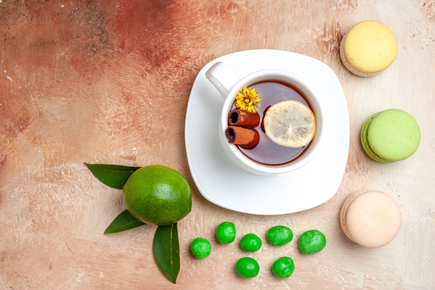 Top view cup of tea with candies and macarons on light brown table tea lemon biscuit