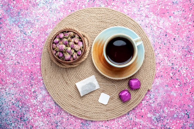 Top view cup of tea with candies on pink background.