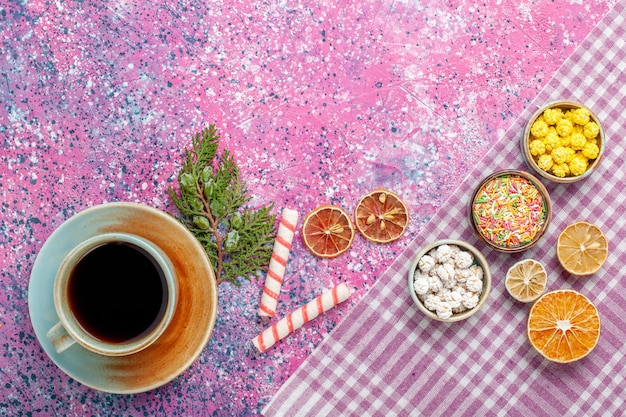 Top view cup of tea with candies on pink desk candy tea drink sweet sugar confiture color