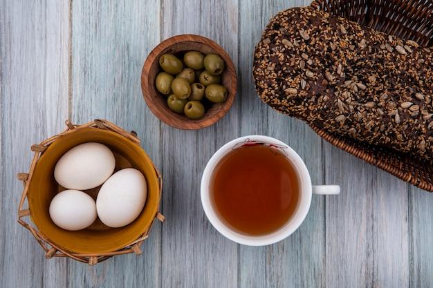 Vista dall'alto tazza di tè con uova di gallina, olive e pane nero su sfondo grigio