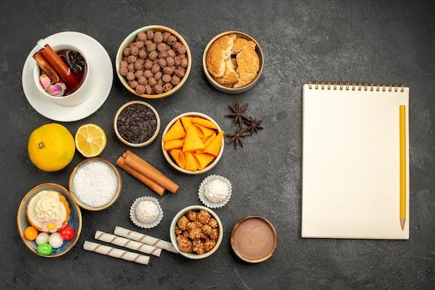 Vista dall'alto tazza di tè con patatine e torta su superficie scura biscotti caramelle biscotto torta torta dolce