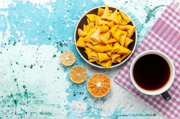 Tazza di tè vista dall'alto con patatine sulla superficie azzurra