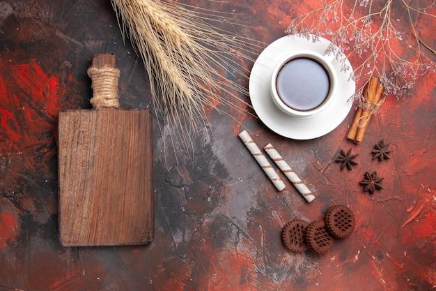 Vista dall'alto tazza di tè con biscotti al cioccolato sul biscotto biscotto da tè pavimento scuro