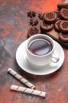 Top view cup of tea with choco cookies on dark table biscuit tea cookie