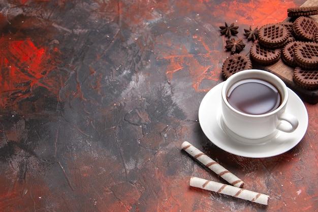 Top view cup of tea with choco cookies on dark table biscuit tea cookies