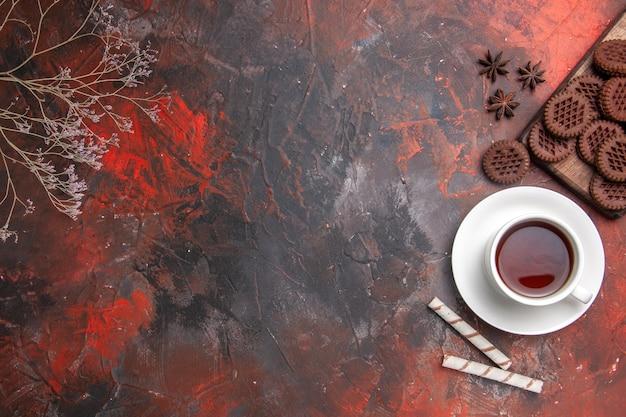 Vista dall'alto tazza di tè con biscotti al cioccolato sul tavolo scuro colore cerimonia tè scuro