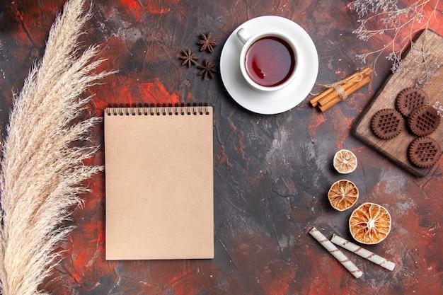 Vista dall'alto tazza di tè con biscotti al cioccolato sul biscotto scuro tavolo scuro