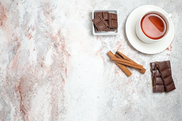 Top view of cup of tea with chocolate bars on white surface