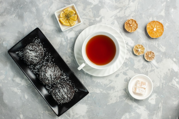 Vista dall'alto tazza di tè con torte al cioccolato sullo scrittorio bianco chiaro