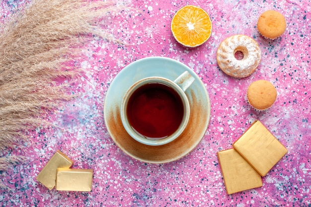 Top view of cup of tea with chocolate candies and cakes on the pink surface
