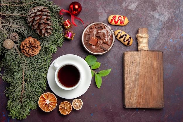 Vista dall'alto tazza di tè con dessert al cioccolato e biscotti su uno spazio buio