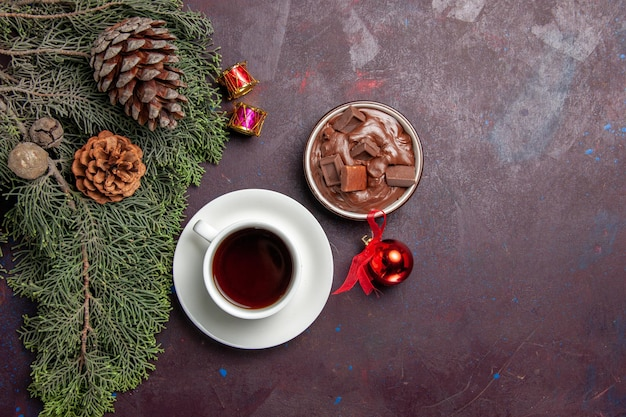 Top view cup of tea with chocolate dessert on dark space