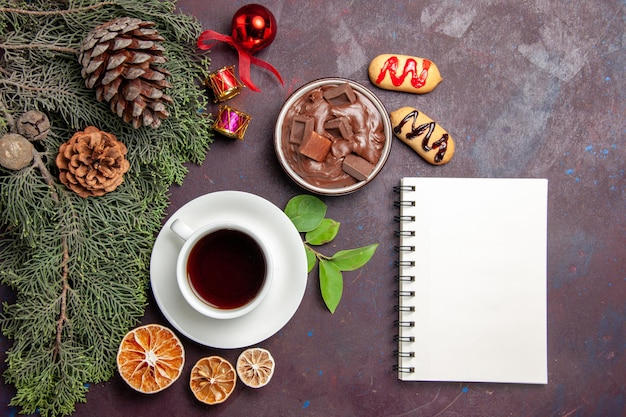 Top view cup of tea with chocolate dessert and notepad on dark space