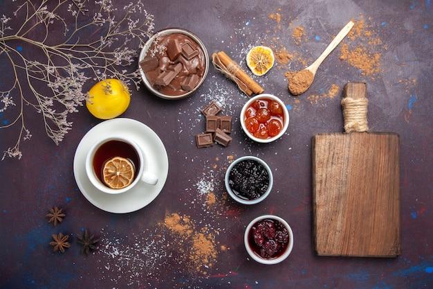 Vista dall'alto tazza di tè con cioccolato e marmellata su uno spazio buio