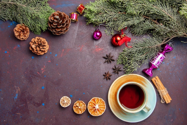 Top view cup of tea with christmas tree on dark space