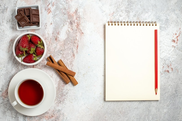 Top view of cup of tea with cinnamon berries on a white surface