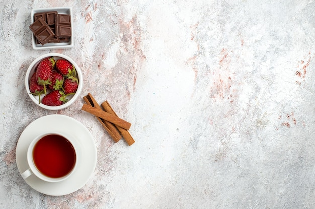 Top view of cup of tea with cinnamon berries on white surface