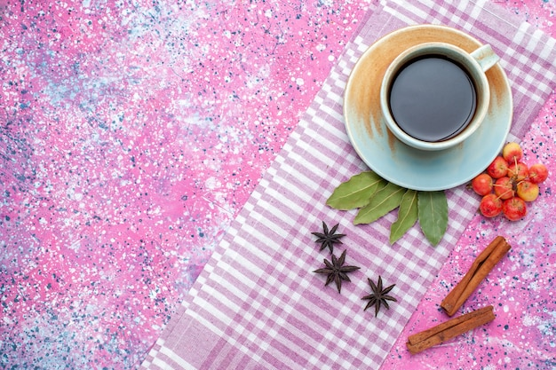 Top view cup of tea with cinnamon and cherries on pink backgruond tea drink fruit color