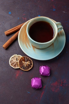Top view of cup of tea with cinnamon and chocolate candies on the dark surface
