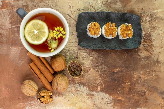 Vista dall'alto tazza di tè con cannella e confetture sulla scrivania leggera