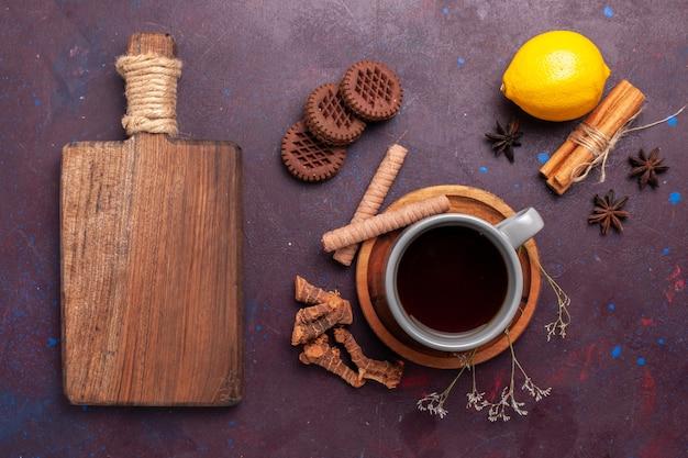 Top view cup of tea with cinnamon cookies and lemon on the dark desk tea sweet color photo