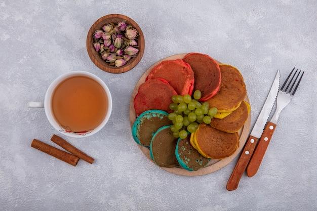 Vista dall'alto tazza di tè con cannella e boccioli secchi in una ciotola con frittelle su un supporto su uno sfondo bianco