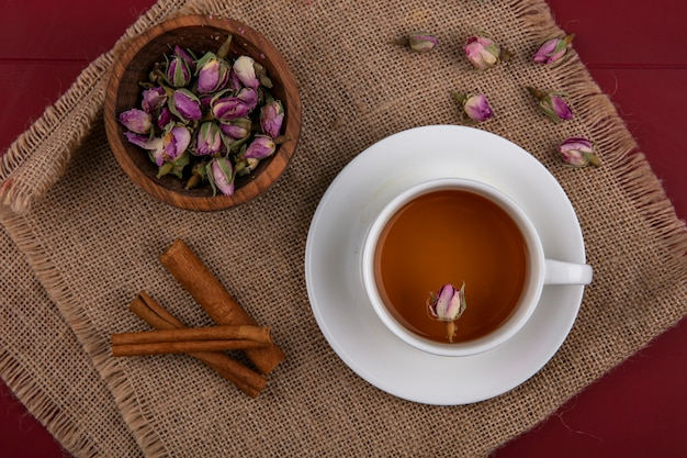 Top view a cup of tea with cinnamon and dry rosebuds on a beige napkin
