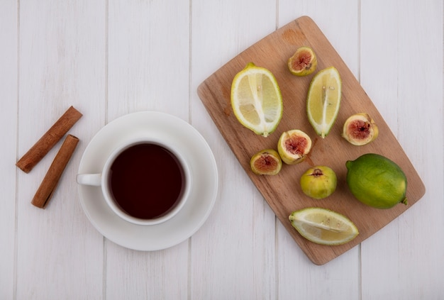 Top view cup of tea with cinnamon and figs with lime slices on a cutting board on white background