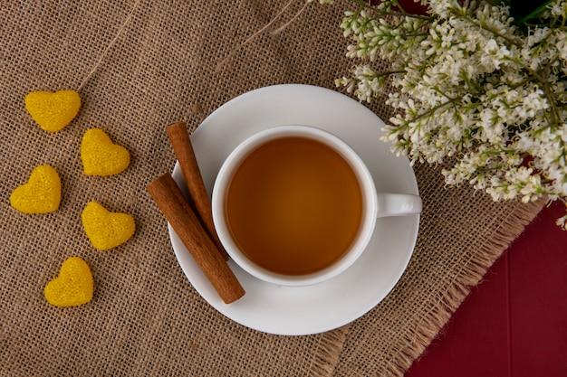 Vista dall'alto della tazza di tè con cannella e fiori su un tovagliolo beige