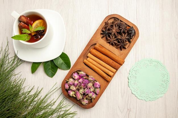 Vista dall'alto tazza di tè con cannella e fiori sul fiore di colore del tè della scrivania bianca
