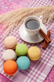 Vista dall'alto tazza di tè con cannella e macarons francesi su zucchero dolce biscotto torta rosa chiaro scrivania