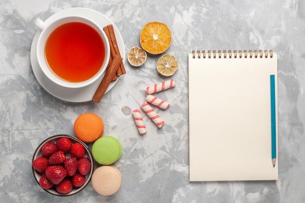 Vista dall'alto tazza di tè con cannella e macarons francesi su superficie bianca