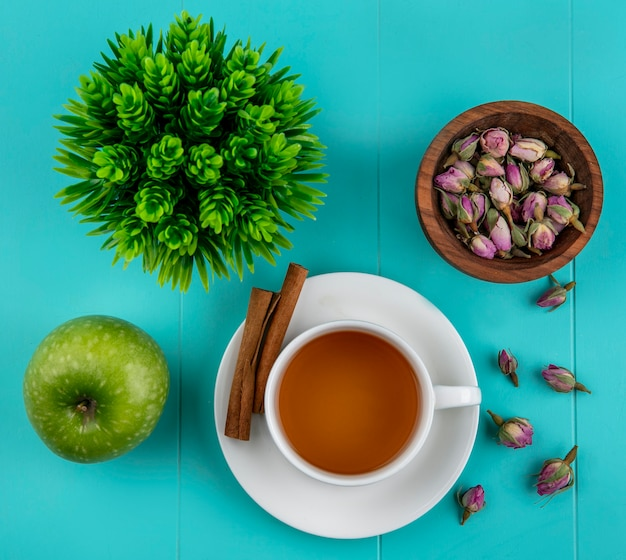 Top view cup of tea with cinnamon green apple and dry rose buds on a blue background