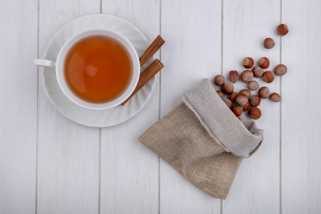 Top view cup of tea with cinnamon and hazelnuts in a burlap bag on a gray background