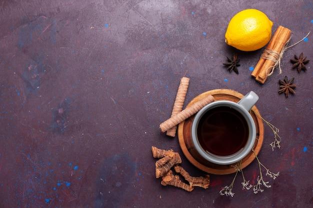 Vista dall'alto tazza di tè con cannella e limone sulla foto a colori dolce del tè scuro della scrivania