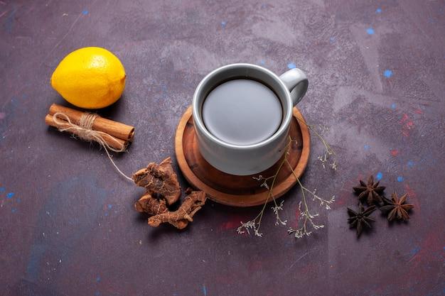 Vista dall'alto tazza di tè con cannella e limone sul colore dolce del tè di superficie scura