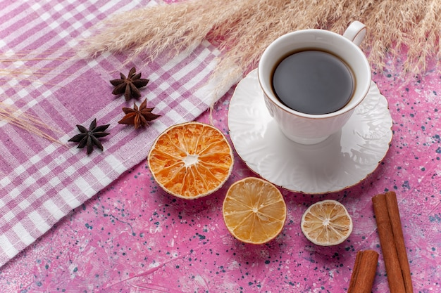 Top view cup of tea with cinnamon and lemon on the pink