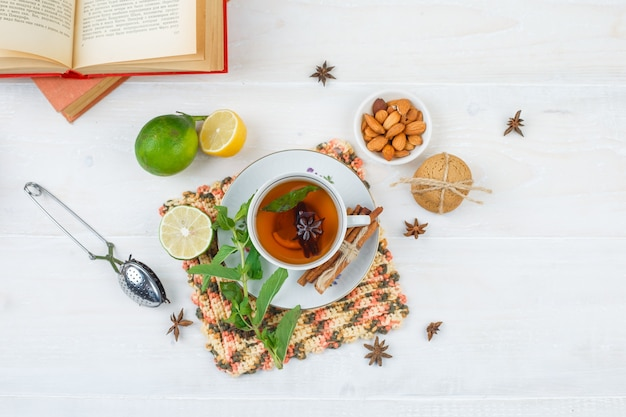 Top view of cup of tea with cinnamon and lemon on square placemat with limes, a bowl of almonds, tea strainer and books on white surface