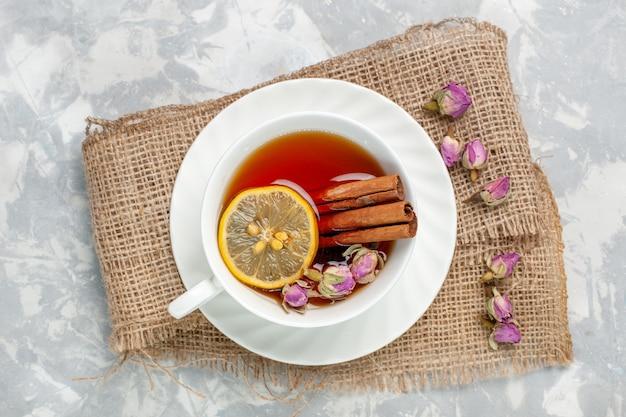 Vista dall'alto tazza di tè con cannella e limone sulla scrivania bianca
