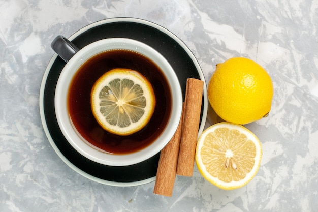 Top view cup of tea with cinnamon and lemon on the white surface