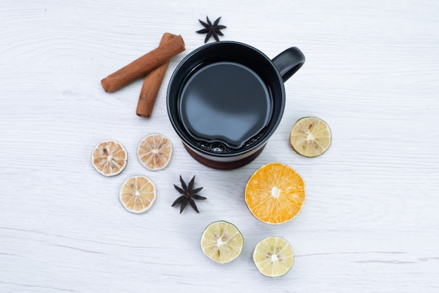 Top view cup of tea with cinnamon and lemon on white