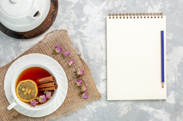 Top view cup of tea with cinnamon notepad and lemon on white surface