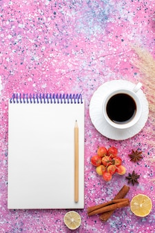 Top view cup of tea with cinnamon and notepad on pink background.